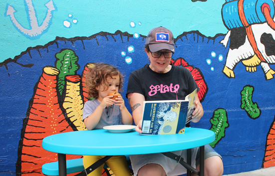 Zingerman's Just For Younger Kids Storytime Tasting - Em reading a book to a toddler eating a blueberry muffin.