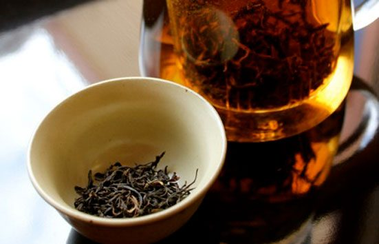 Zingerman's Tea Steeping Next To A Cup Of Leaves