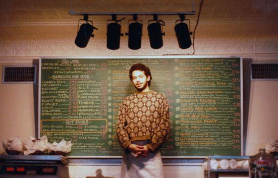 Ari standing in front of Zingerman's Deli menu