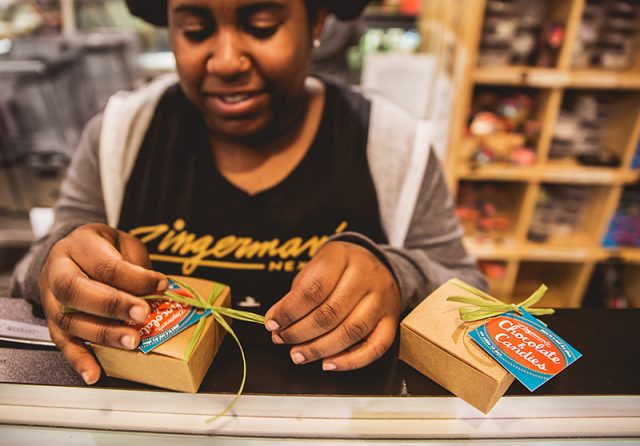 Zingerman's staff making a custom truffle box with ribbon