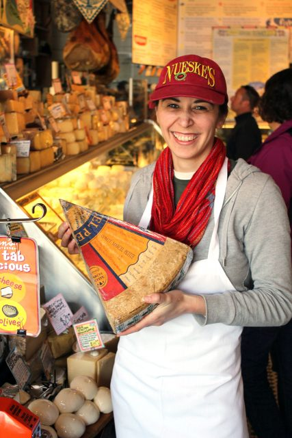 Zingerman's staff holding up a slice of Extra Aged Comté