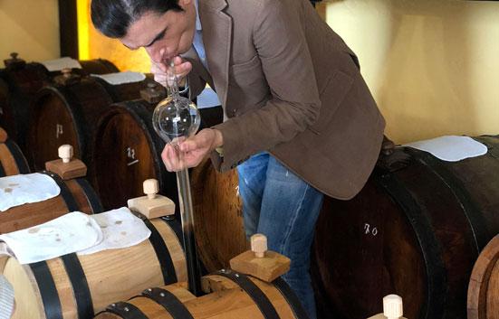 Simone Tintori of La Vecchia Dispensa siphoning balsamic vinegar from a barrel
