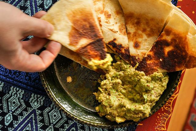Épices de Cru cumin quesadillas with a hand dipping them in guacamole