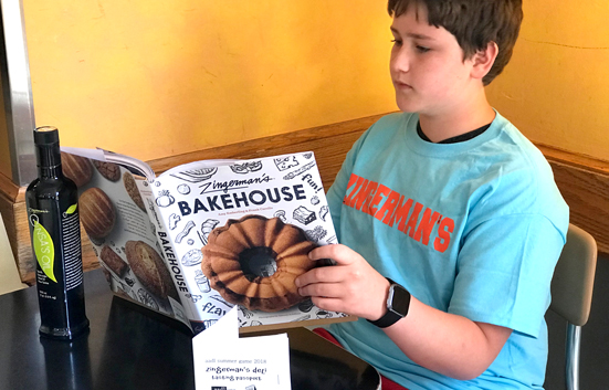 Reading the Zingerman's Bakehouse Cookbook at a table with a Ann Arbor Library Summer Game passport