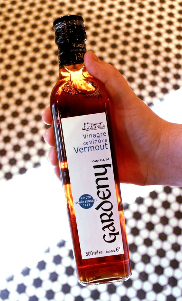 Gardeny Vermouth Vinegar in a hand with the Deli tile floor as a background