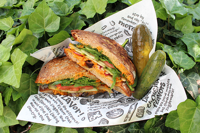 Vegetarian sandwich arranged in sandwich basket with two pickles surrounded by ivy