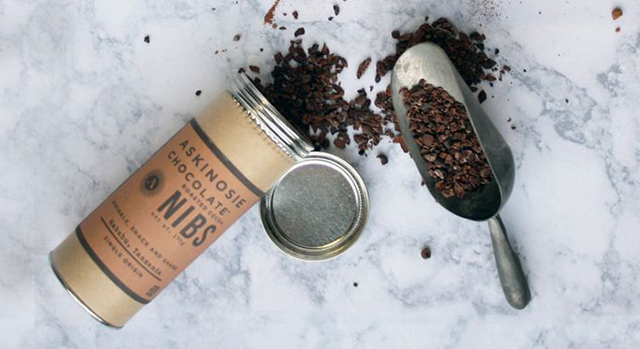 A tin of Askinosie Chocolate cocoa nibs spilled out and displayed in a scoop on marble surface