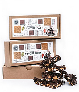 Pieces of chocolate s'more bark pictured next to decorative gift boxes