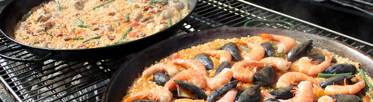 Zingerman's Deli pans of paella cooking over a mesquite grill