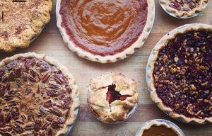 A top-view of fall pies in different sizes arranged on butcher block