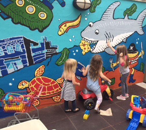 Kiddos playing in Zingerman's Deli play area in front of an underwater mural