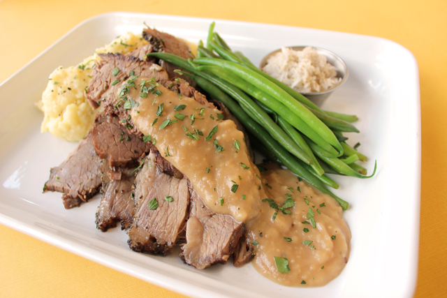 Zingerman's Deli beef brisket on a plate with gravy, green beans and mashed potatoes
