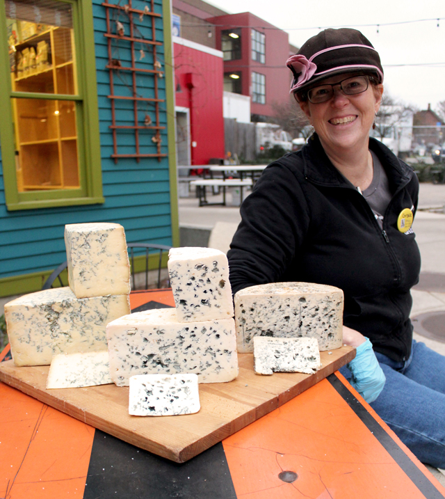 Zingerman's Managing Partner, Grace Singleton, with a spread of blue cheeses on a cutting board, outside of the Deli
