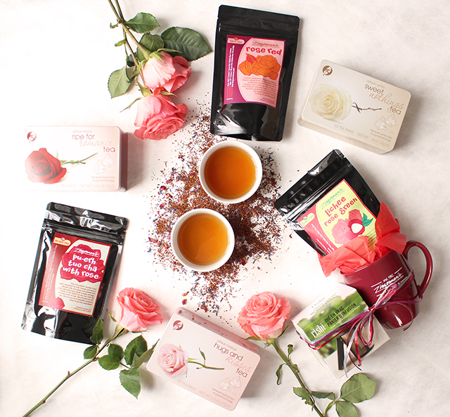 Gift boxes and gift bags of tea arranged with pink roses and two cups of tea