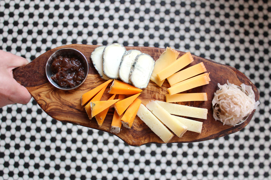 Zingerman's Deli staff holding a cheesemonger board with a variety of cheese and pairings, how to build cheeseboard