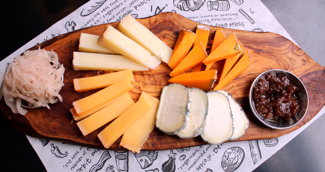Zingerman's Cheeseboard with a variety of cheese and pairings on a wooden board