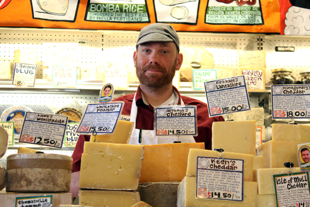 Zingerman's Deli Cheesemonger behind a mountain of cheese in the retail cheese area