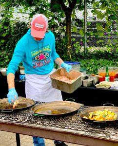 Deli Chef preparing paella pans for rice over a grill